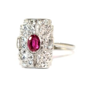 From Thomas Glover : Art Deco Ruby & Diamond Tablet Ring c.1925 SKU: RR033 £3,950.00Price A fabulous piece from the At Deco era. This beautiful ring is set with a bright red oval ruby to the centre within a finely crafted diamond set tablet with a combination of old-cut and baguette diamonds set in a typically curved design with a low set geometric underbezel. The ring is low set to the finger with a fine plain shank typical of this tablet design.